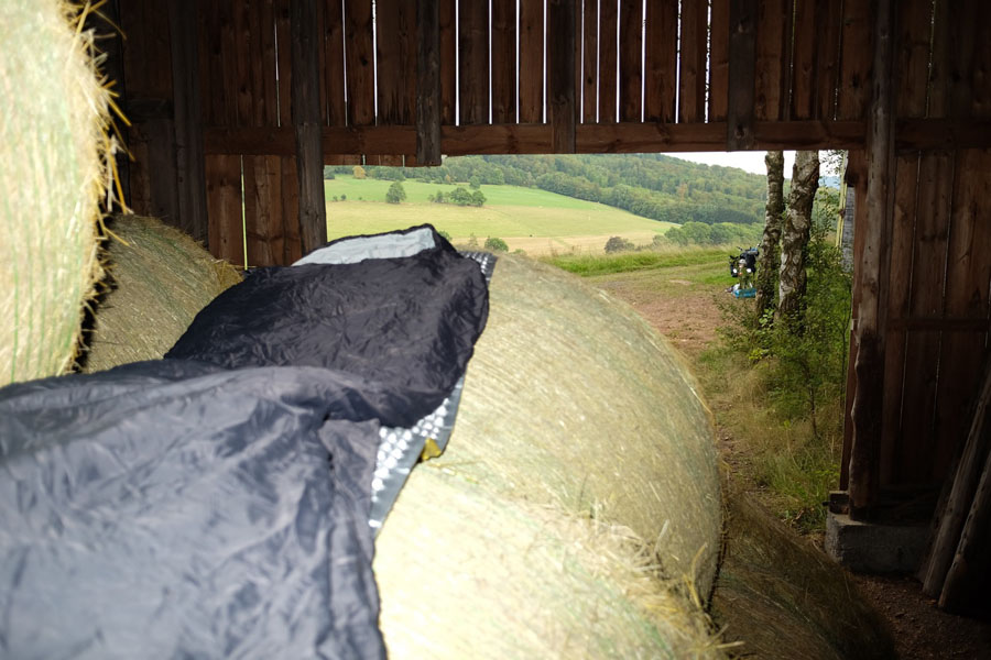 Sleeping among hay bales during my cycling tour.